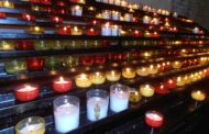 Why do Catholics light votive candles?