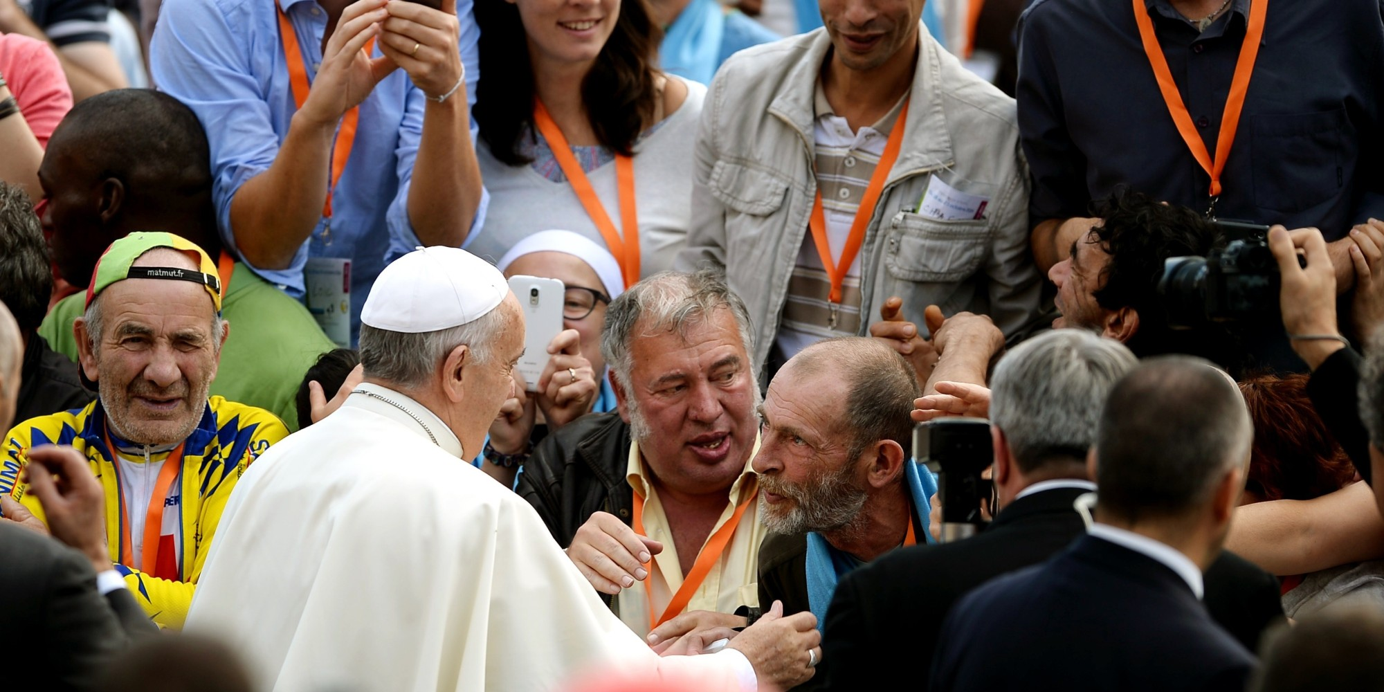French homeless from different French cities, shake hands with Pope Francis upon his arrival for his weekly general audience in St Peter's square at the Vatican on October 22, 2014.  AFP PHOTO / FILIPPO MONTEFORTE        (Photo credit should read FILIPPO MONTEFORTE/AFP/Getty Images)
